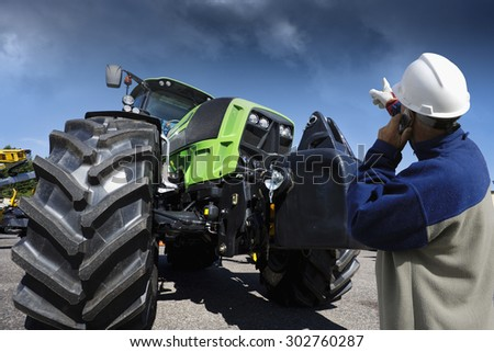 farmer, mechanic pointing at his farming tractor, latest model - stock photo