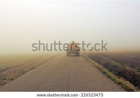 Farmer  morning Autumn road in the fog - stock photo