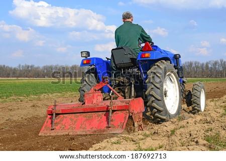 Farmer on tractor handles field  - stock photo