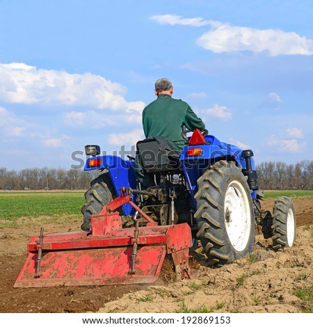 Farmer on tractor handles field  - stock photo