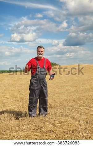 Farmer or agronomist in wheat field after harvest gesturing with tablet in hand - stock photo