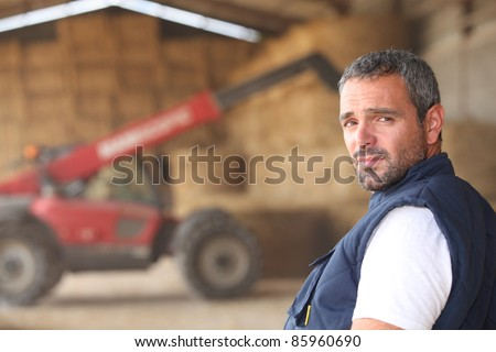 farmer posing in front of a tractor - stock photo