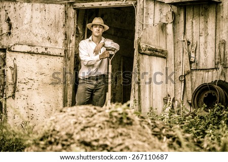 Farmer Shoveling the Horse Manure out of the Barn - stock photo