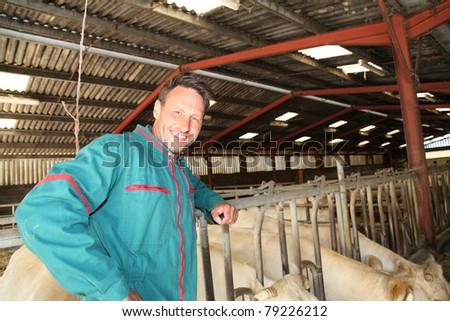 Farmer standing in barn - stock photo