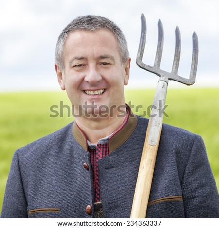 Farmer standing in his field - stock photo
