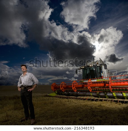 Farmer standing next to combine harvester in wheat field - stock photo