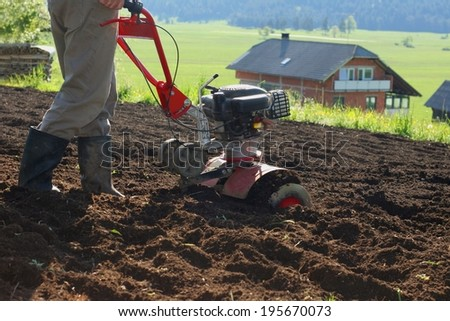 Farmer using modern mechanical rotary tiller with plow on a sunny day in a small farm - stock photo