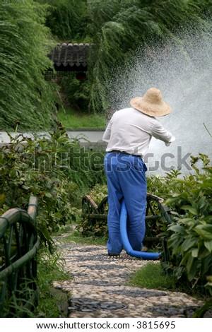farmer watering crops - stock photo