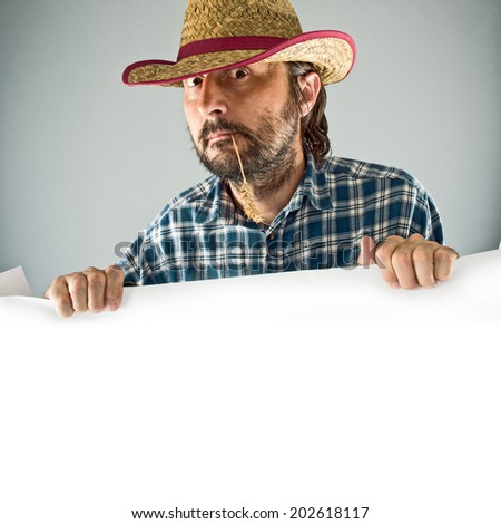 Farmer with cowboy straw hat holding blank poster as copy space - stock photo