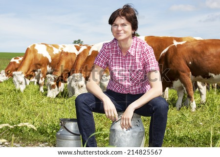 Farmer with milk churns at their cows - stock photo