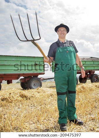 Farmer with pitchfork on the field - stock photo