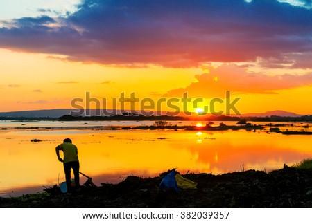 Farmer work and sunset on lagoon in countryside, Sakon Nakhon Thaialnd - stock photo