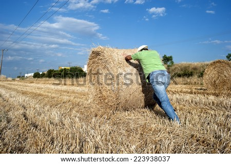 Farmer working at his farmland at the end of summer - stock photo
