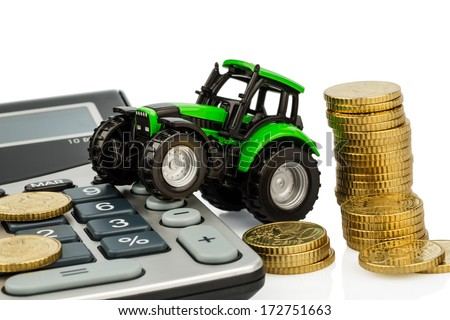 farmers in agriculture have to reckon with rising costs. higher prices for feed, fertilizer and plants. tractor with coins and calculator - stock photo