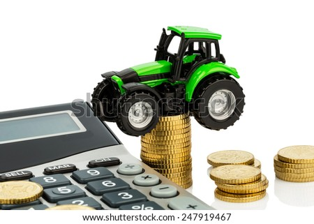 farmers in agriculture have to reckon with rising costs. higher prices for food, fertilizer and plants. tractor with coins and calculator - stock photo