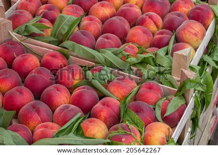 Farmers market peaches in a wooden crates. At the farmers market local growers come and sell their freshly picked crops at reasonable prices. Selective focus. - stock photo