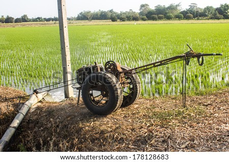 Farmers Pumping water to Jasmine rice fields with Thai tractor - stock photo