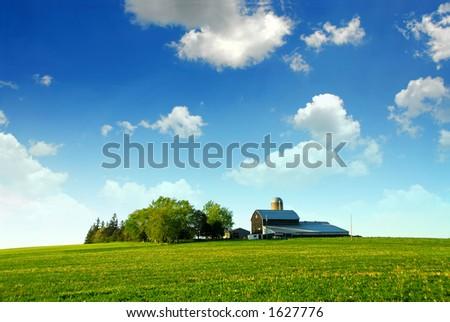 Farmhouse and barn among green fields - stock photo