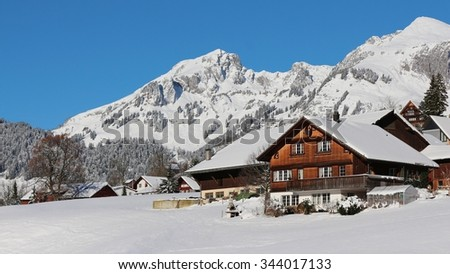 Farmhouse in the Swiss Alps and snow covered mountains - stock photo