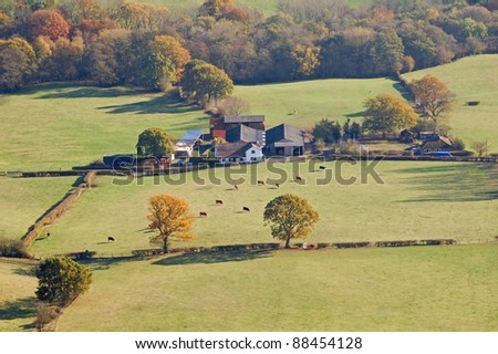 farmhouse set amidst fields in rural england - stock photo