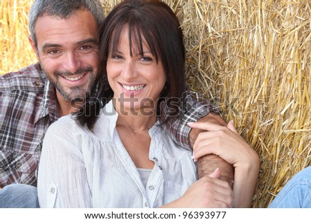 Farming couple sitting in the hay - stock photo