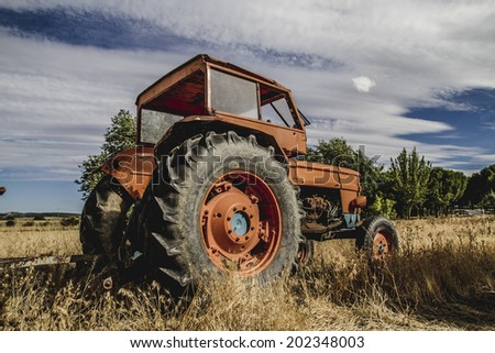 farming, old agricultural tractor abandoned in a farm field - stock photo