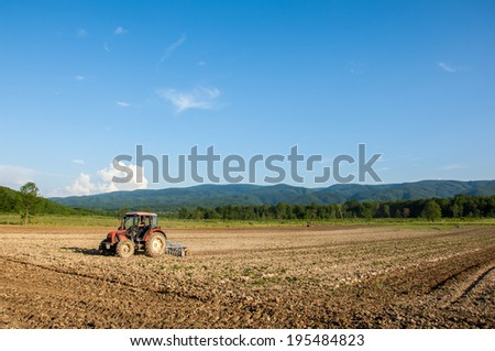 Farming with tractor and plow in field with mountain Papuk in the background, Croatia. - stock photo