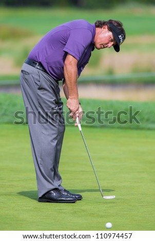 FARMINGDALE, NY - AUGUST 21: Phil Michelson hits a putt at Bethpage Black during the Barclays on August 21, 2012 in Farmingdale, NY. - stock photo