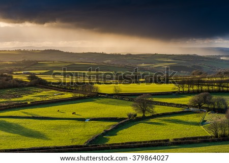 Farmland and coutryside with stormy clouds rolling with pouring rain at sunset. View from hill top, long shadows. - stock photo
