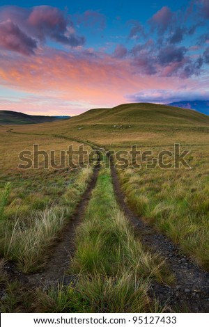Farmland covered in green grass high up in the Drakensberg Mountain range in South Africa - stock photo