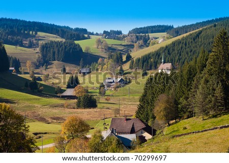 Farmland, farmhouses with chapel and forested hills in Black Forest, rural Germany. - stock photo