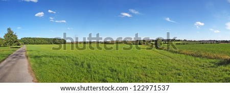 farmland panorama with pathway, green meadows, and blue sky - stock photo