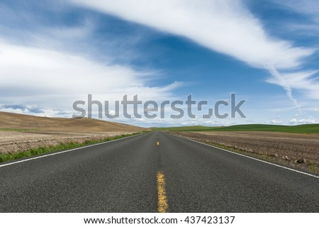 Farmland Road to the Horizon. A lonely road in the palouse area of eastern Washington state seems to go on forever through plowed fields and wheat crops with blue skies and lovely clouds. - stock photo