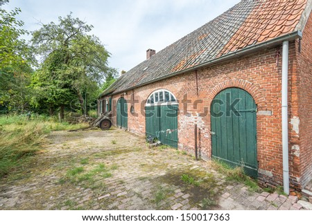 Farmyard of an old and weathered farm in the Netherlands. - stock photo