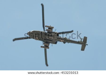 FARNBOROUGH, UK - JULY 14: Underside of a Boeing AH-64 Apache helicopter gunship arriving in a clear blue sky at Farnborough, UK on July 14, 2016 - stock photo
