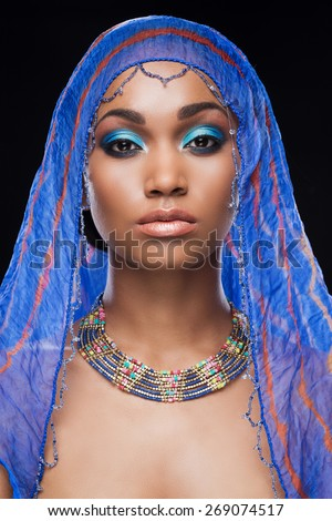 Fascinating beauty. Beautiful African woman covering head by scarf and looking at camera while standing against black background - stock photo