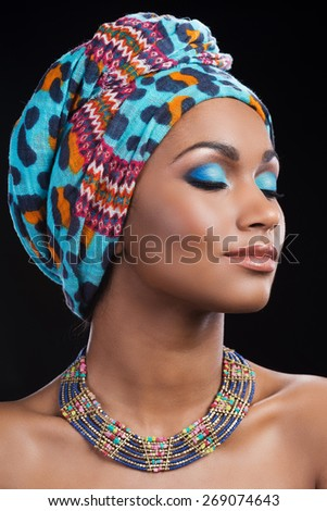 Fascinating beauty. Beautiful African woman wearing a headscarf and necklace keeping eyes closed while standing against black background - stock photo