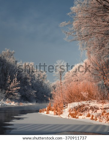 Fascinating winter landscape. Frosty, misty morning on the small river. frost covered trees in the warm glow of sunrise on the beach. Eastern Europe. Ukraine  frozen lake and trees in snow - stock photo