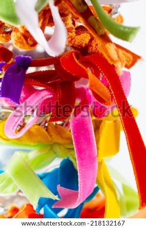 Fashion accessories: very colourful bracelets made by weaving velvet ribbons and metal chains together. - stock photo
