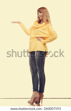 Fashion and advertisement concept. Full length woman holding open palm empty hand showing copy space for product - stock photo