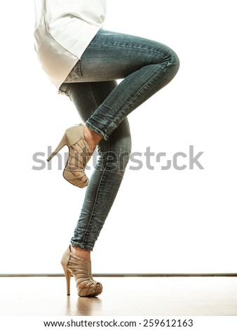Fashion and people concept. Woman legs in denim trousers platform high heels shoes casual style, dancing pose isolated on white background - stock photo