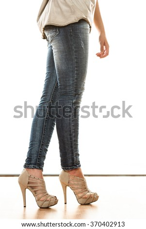 Fashion and people concept. Woman legs in denim trousers platform high heels shoes casual style isolated on white background - stock photo
