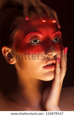 Fashion Art Concept. Beauty Woman Face with Red Painted Mask - stock photo