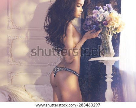 Fashion art photo of beautiful lady with flowers. Home interior. Morning - stock photo