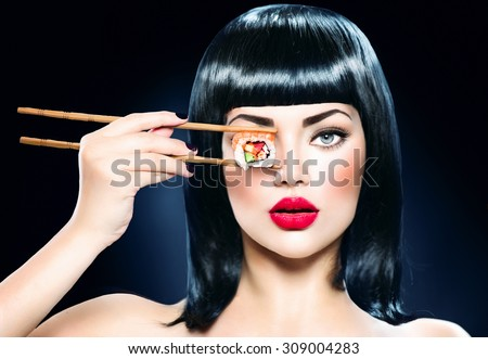 Fashion art portrait of beauty model girl eating Sushi roll, healthy japanese food. Beautiful woman holding chopsticks with sushi. Sexy lady - stock photo
