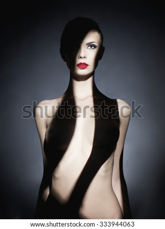 Fashion art studio portrait of elegant naked lady with shadow on her body - stock photo