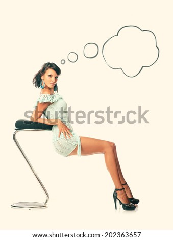 Fashion beautiful brunette model sitting on a stool with thinking bubble. - stock photo