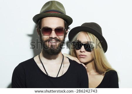 fashion beautiful couple in hat wearing trendy glasses and posing over white background together. Hipster boy and girl. Bearded young man and blonde in sunglasses - stock photo