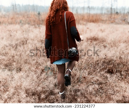 Fashion beautiful girl hipster goes to share with a camera on his shoulder - stock photo