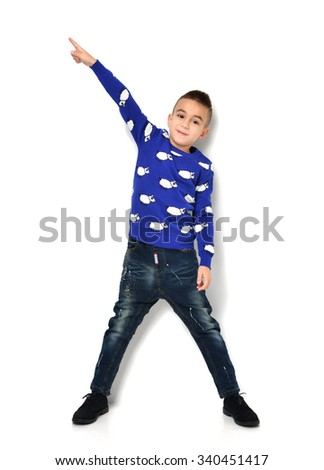 Fashion beautiful little boy in blue cloth jeans standing and pointing finger at the corner over white background - stock photo